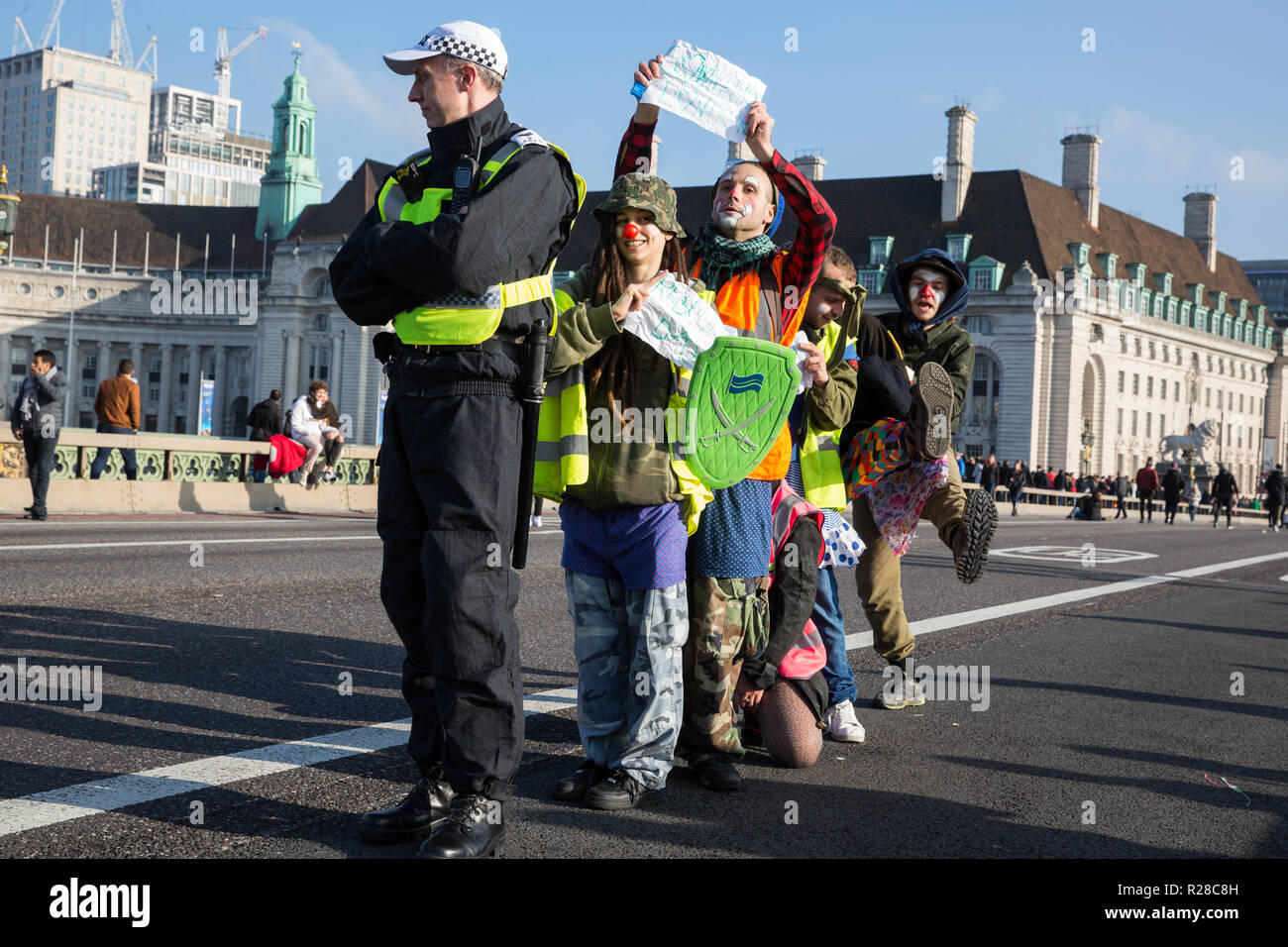 London, UK. 17th November, 2018. Clowns from Clandestine Insurgent Rebel Clown Army (CIRCA) support Extinction Rebellion blocking Westminster Bridge, one of five bridges blocked in central London, as part of a Rebellion Day event to highlight 'criminal inaction in the face of climate change catastrophe and ecological collapse' by the UK Government as part of a programme of civil disobedience during which scores of campaigners have been arrested. Credit: Mark Kerrison/Alamy Live News Stock Photo