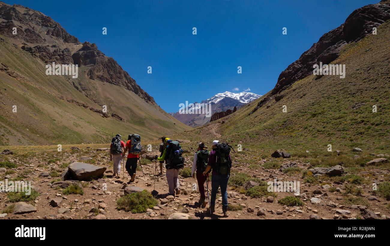 Group of tourists walking towards the Aconcagua mountain in the Aconcagua Provincial Park in the province of Mendoza in Argentina - Stock Image