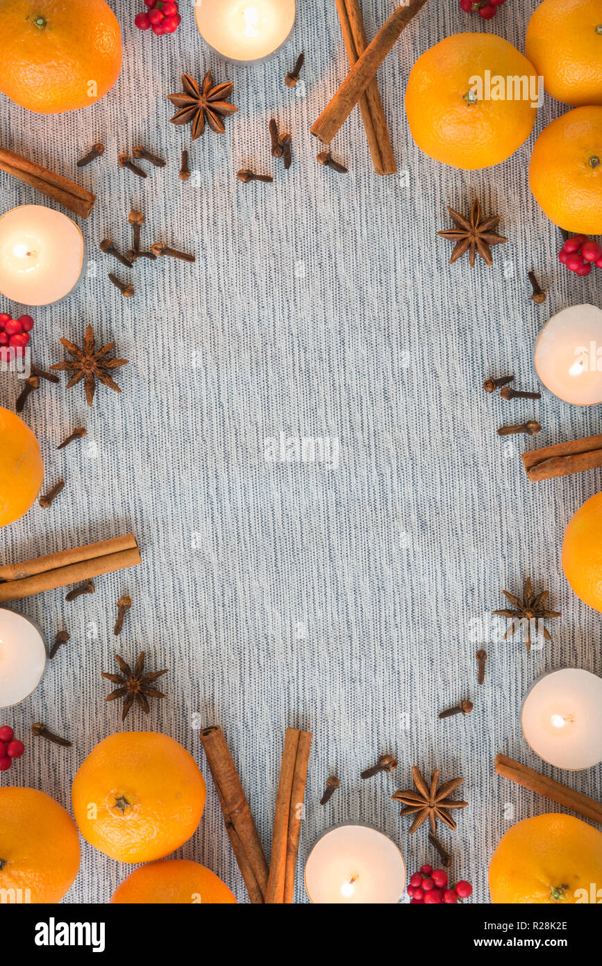 Flat lay Christmas frame of oranges, spices, and candles - Stock Image