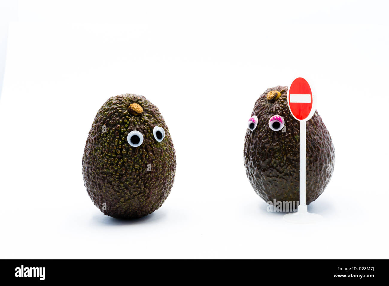Romantic avocados couple with googly eyes as man and woman, traffic no entry sign, funny food concept for creative projects. - Stock Image