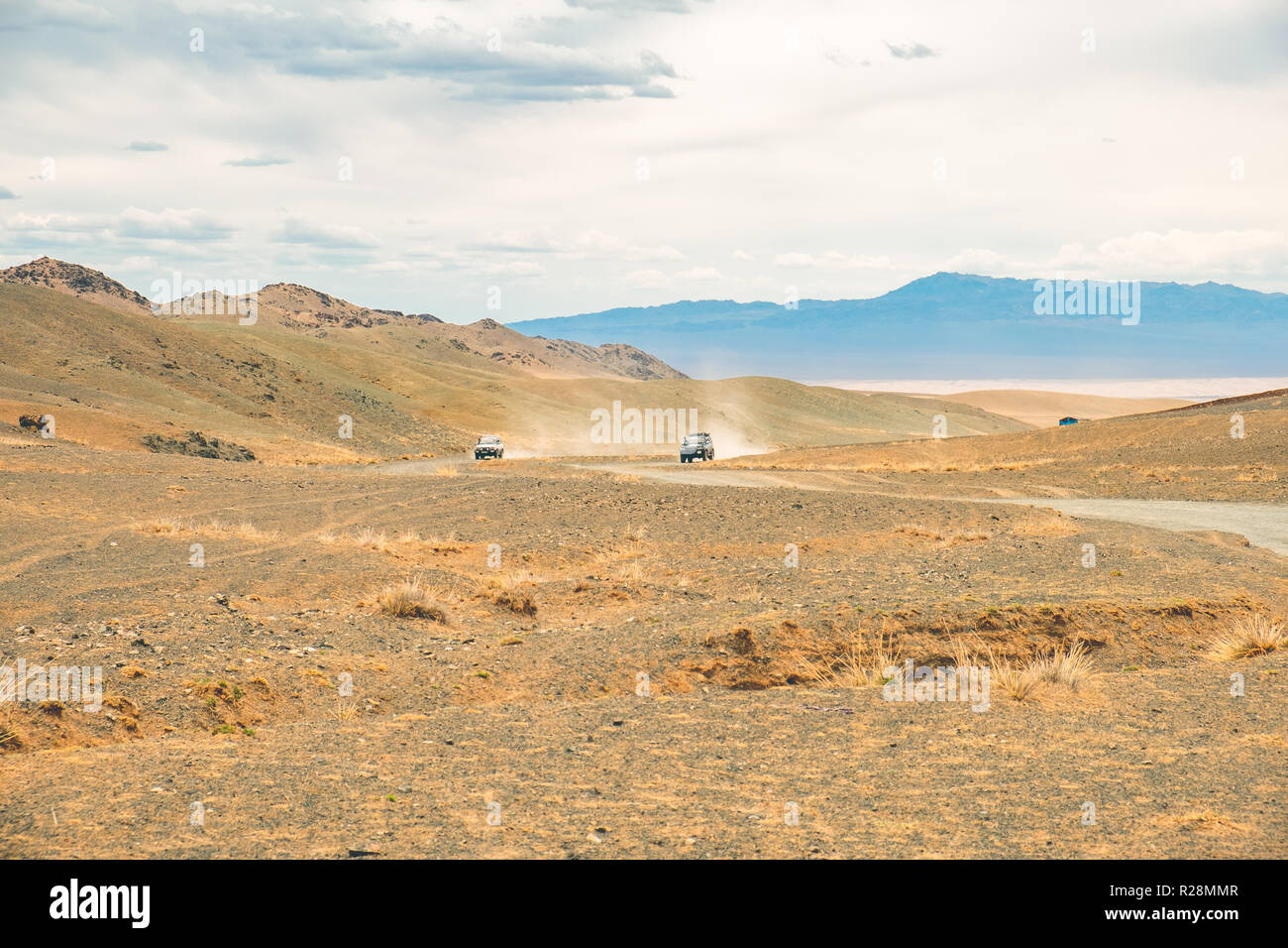 Fast approaching cars with dust trails driving on rugged terrain in Gobi desert, Mongolia. - Stock Image