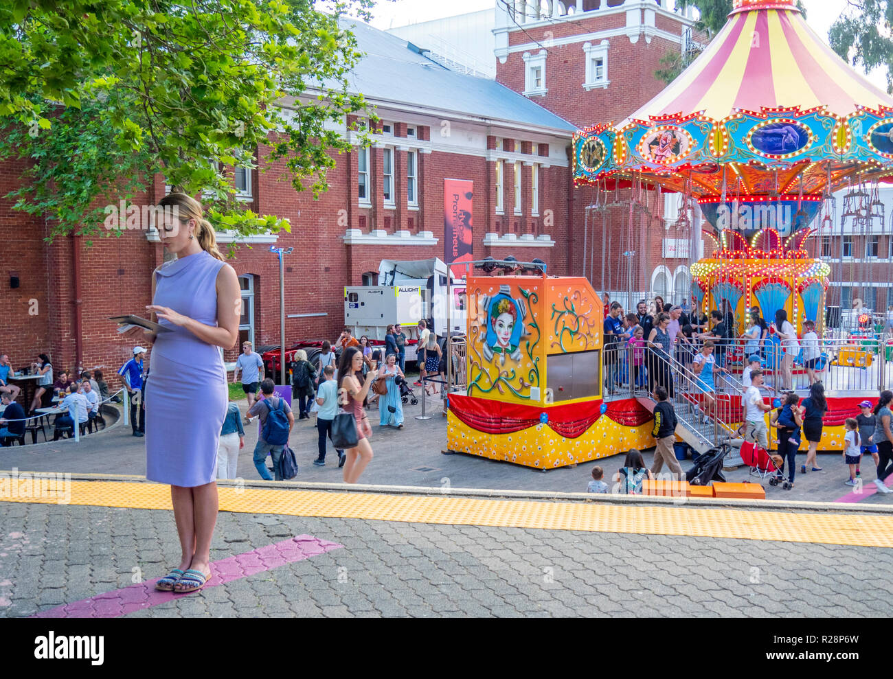 Female television presenter standing by carousel in Perth Cultural Centre Western Australia. - Stock Image