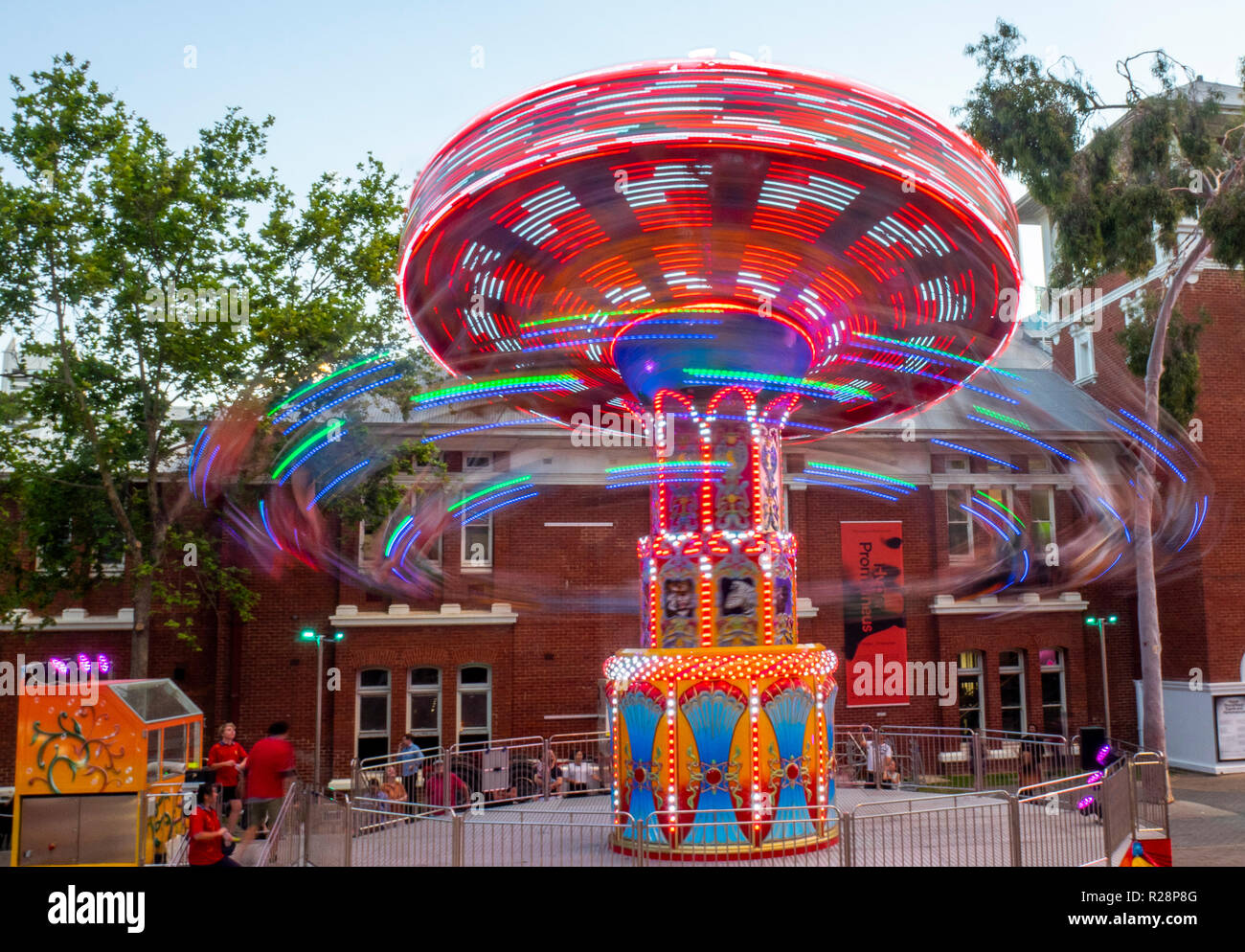 People riding a swing carousel ride Christmas festival Perth Cultural Centre Perth Western Australia. - Stock Image