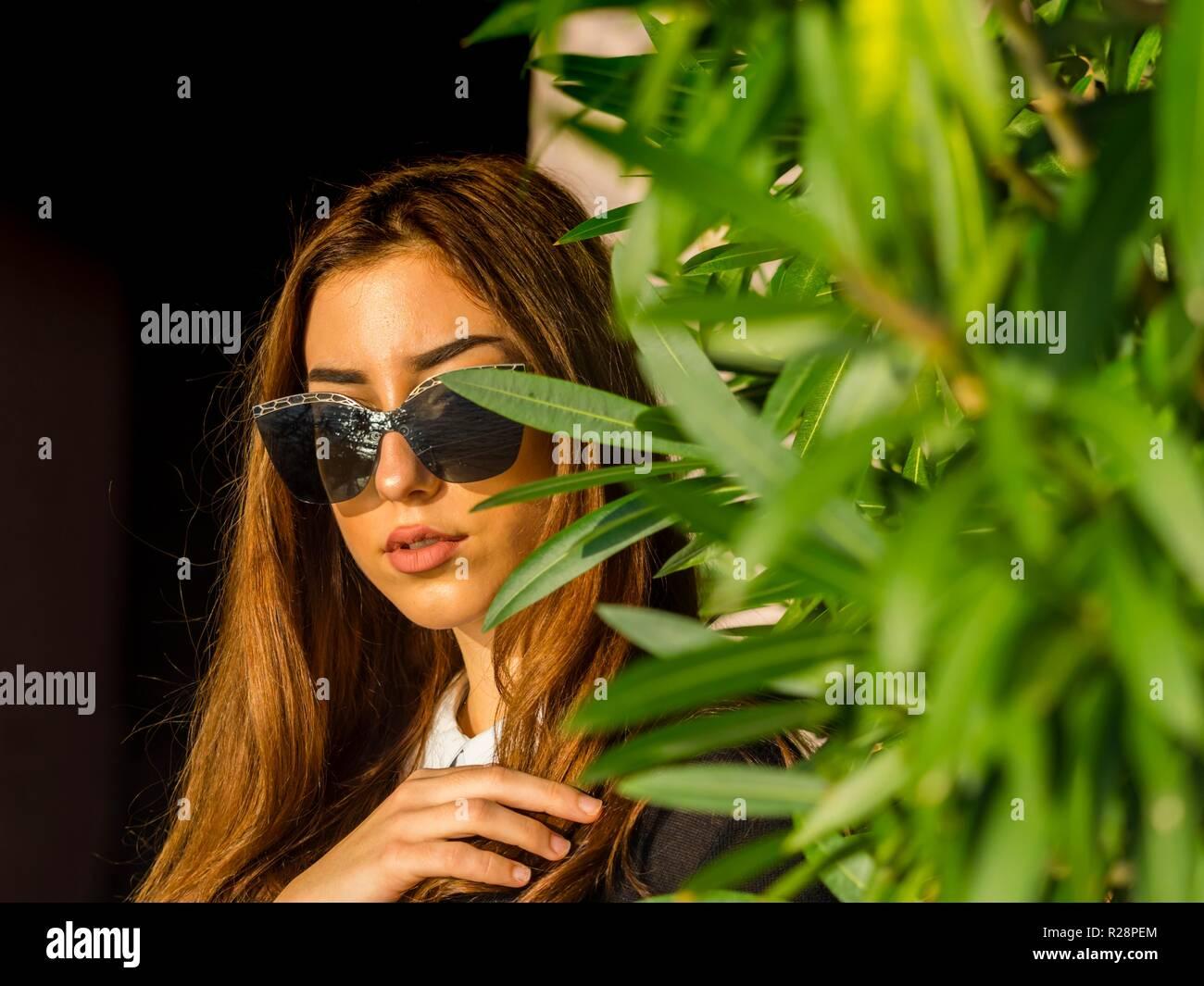 Teen girl hiding behind tree - Stock Image