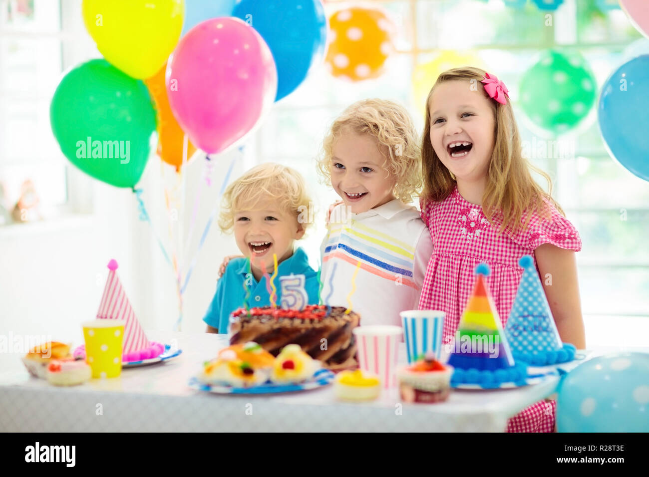 Kids Birthday Party Child Blowing Out Candles On Colorful Cake Decorated Home With Rainbow Flag Banners Balloons Farm Animals Theme Celebration L