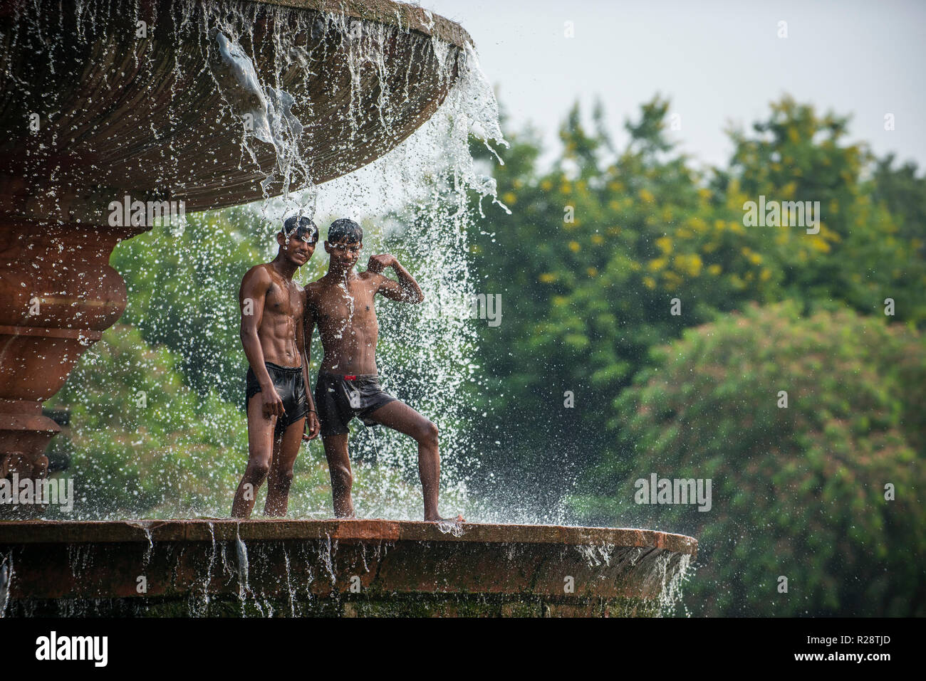 A group of boys and young men cool off in the fountain near the India Gate, a war memorial in New Delhi, India. Stock Photo