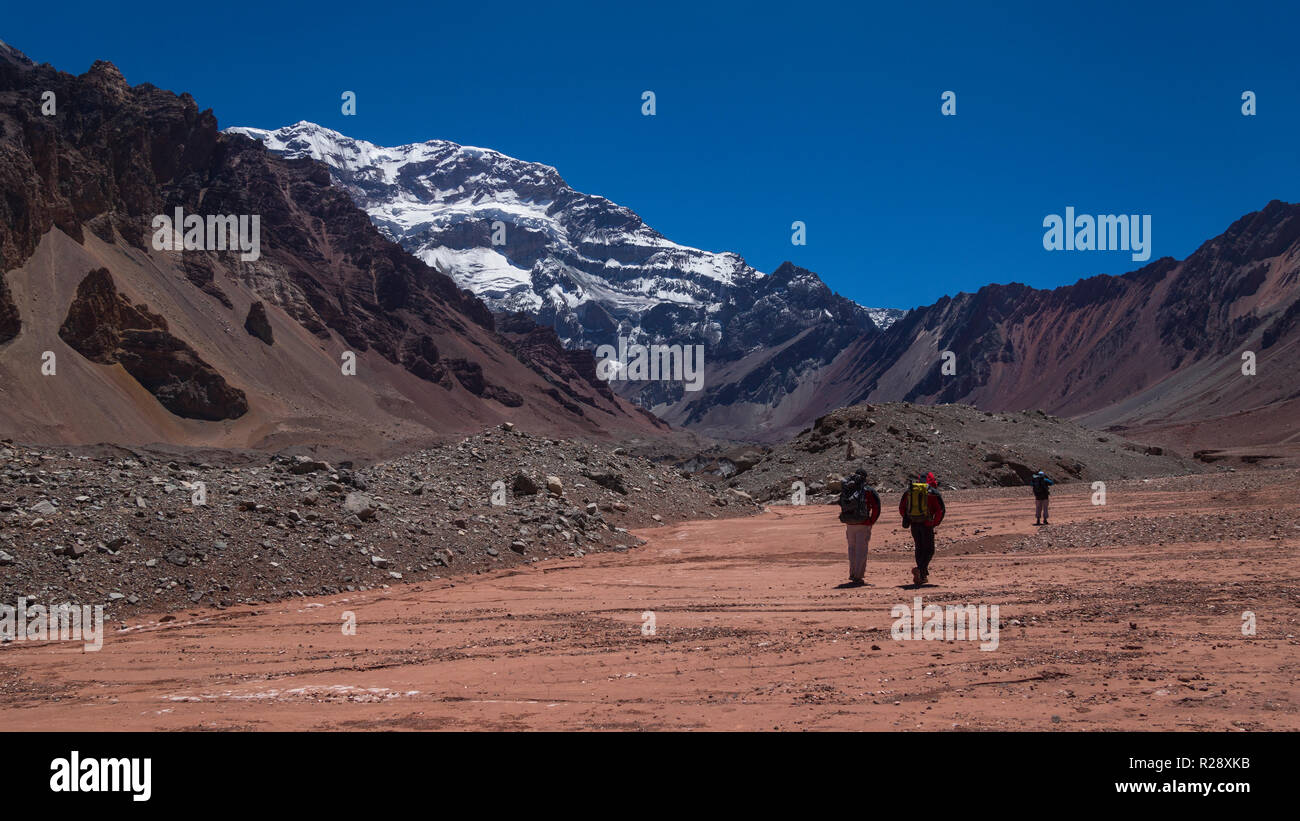 Group of tourists walking towards the south side of the Aconcagua mountain in the Aconcagua Provincial Park in the province of Mendoza in Argentina - Stock Image