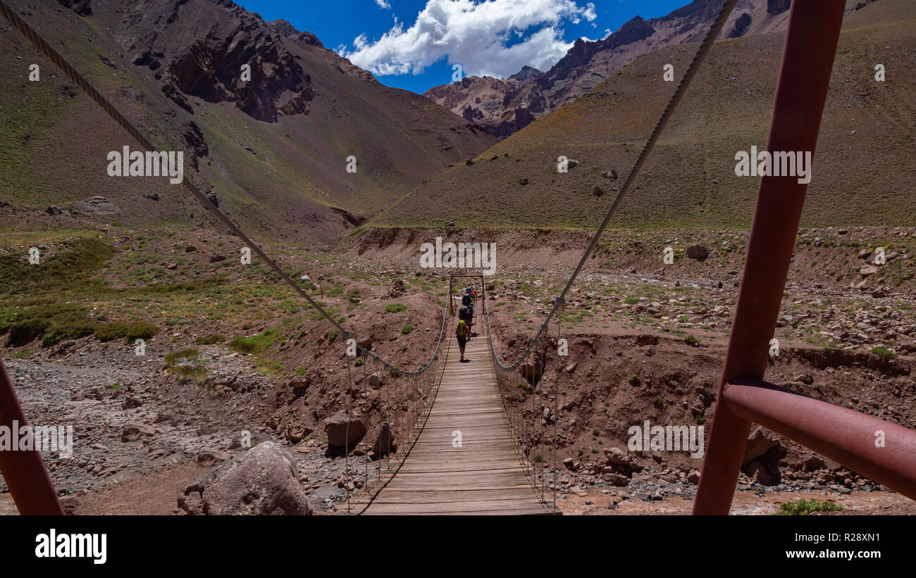 Group of tourists crossing a suspension bridge in the Aconcagua Provincial Park in the province of Mendoza in Argentina - Stock Image