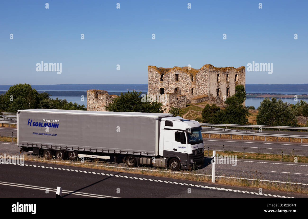 Granna, Sweden - June 26, 2018: The freeway numer E4 with truck in front of the Brhaehus castle ruins overlooking lake Vattern. - Stock Image