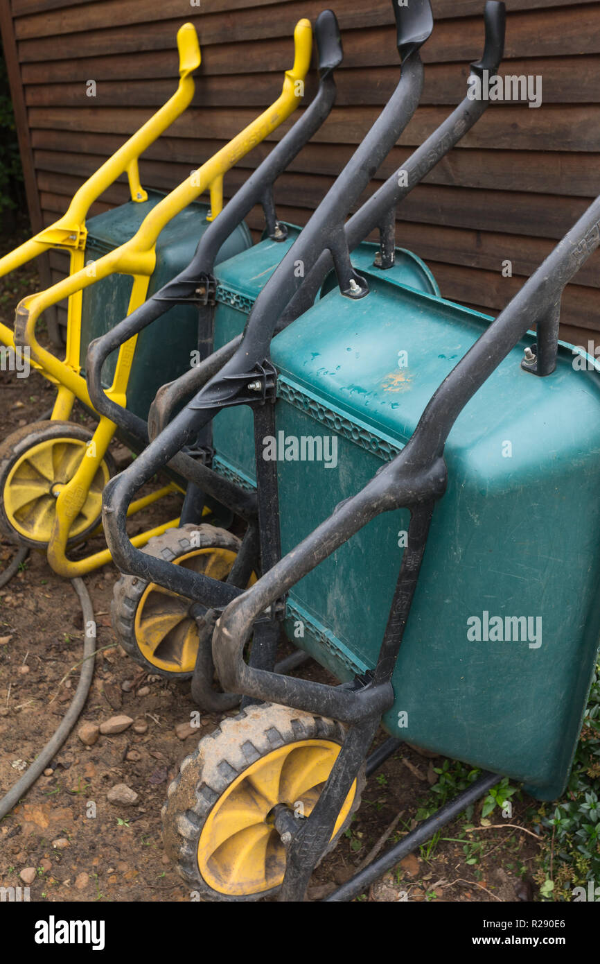 b70e43b54cb three toughened plastic wheelbarrows lined up and resting or leaning against  wooden shed wall in garden