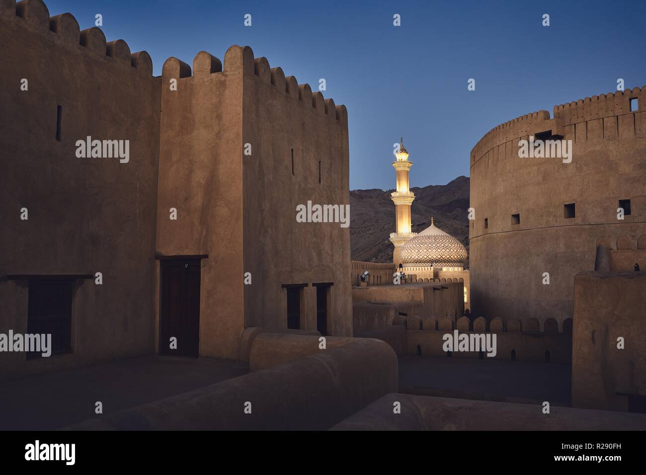 Evening view between watchtowers of historic fort to illuminated mosque. Nizwa, Sultanate of Oman. - Stock Image