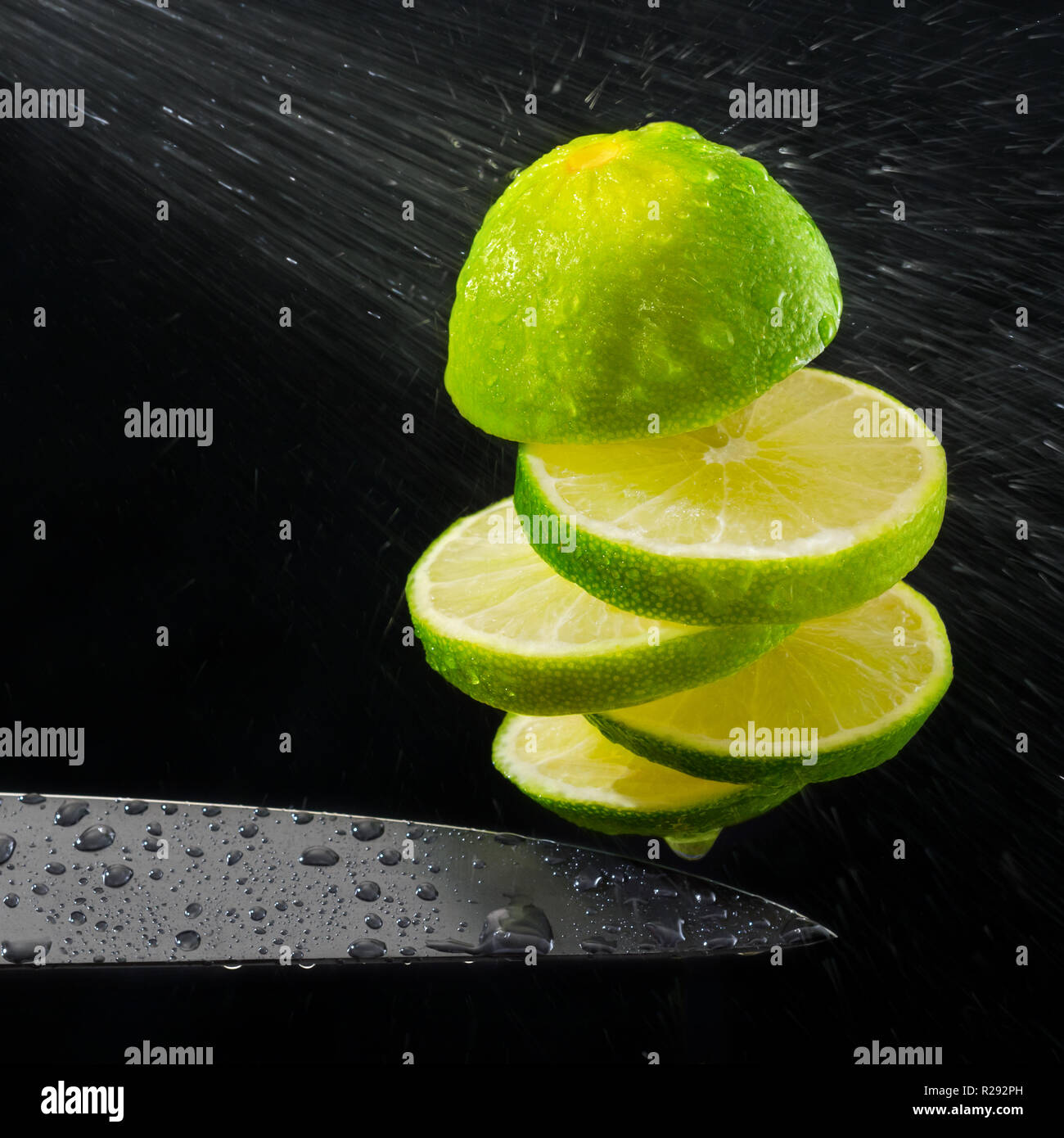 Green lemon cut on the fly, water spray. Stock Photo