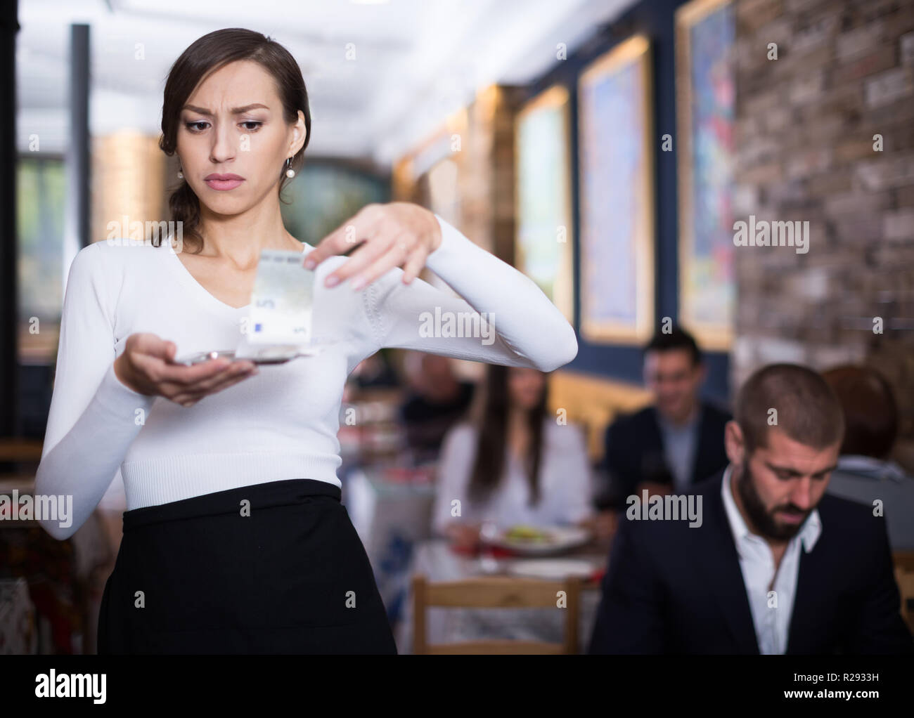 Surprised waitress woman  considering  a tray with money in a restaurant - Stock Image
