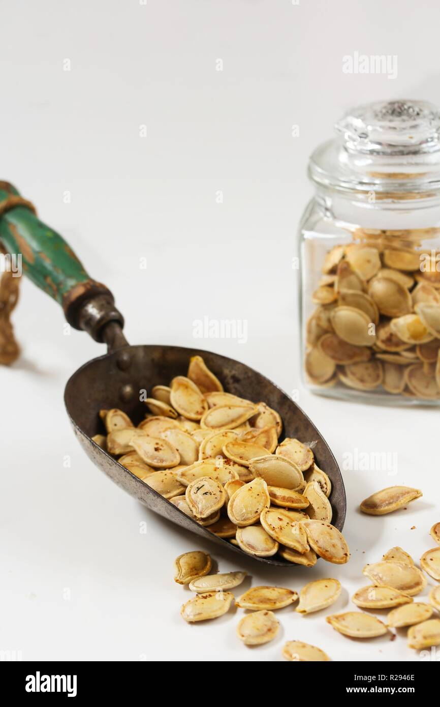 Baked pumpkin seeds in a metal scoop on white background Stock Photo