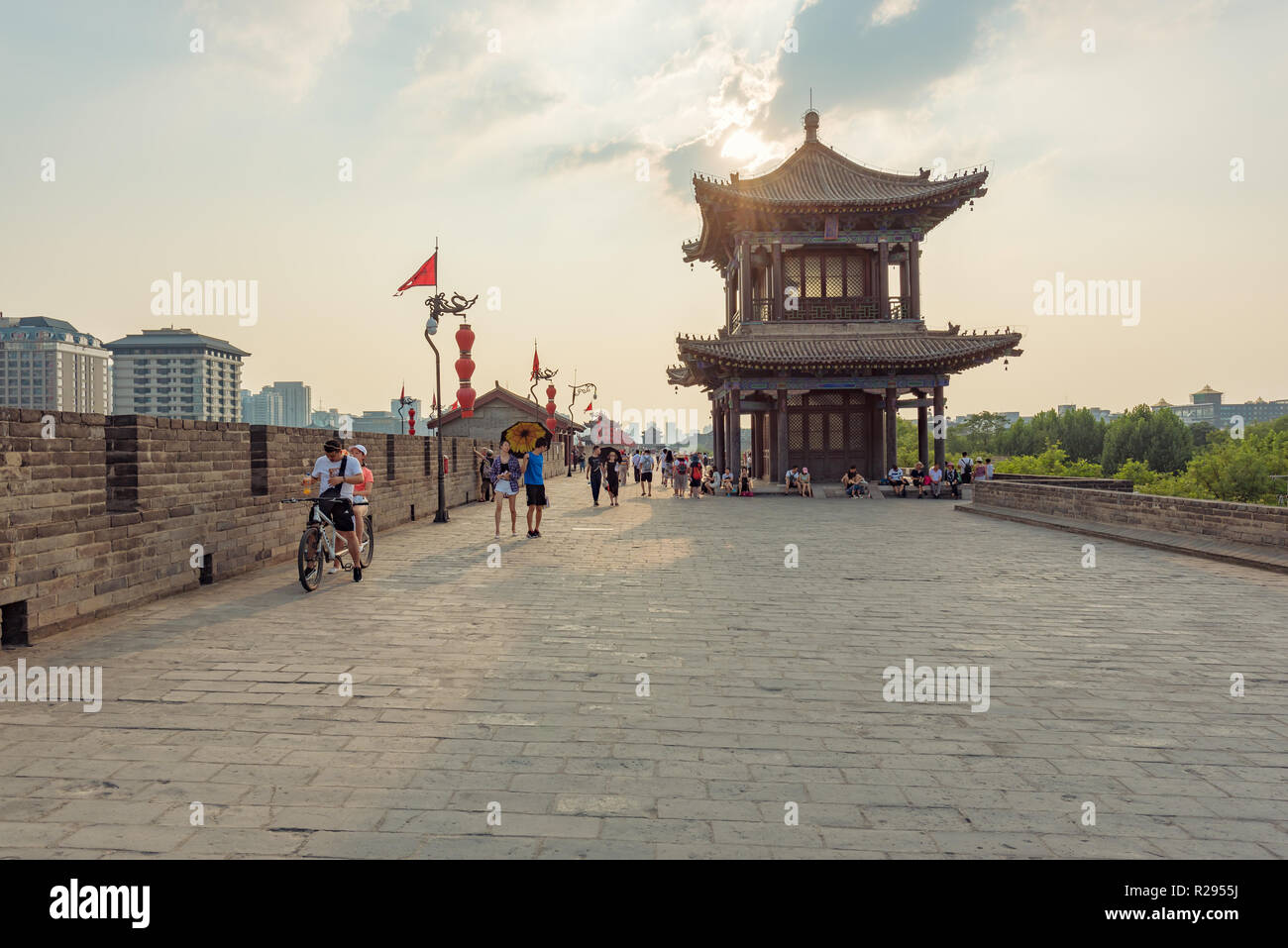 Xi'an, Shaanxi province, China - Aug 8, 2018 : People walking and riding bicycle on the city fortified wall in late afternoon - Stock Image
