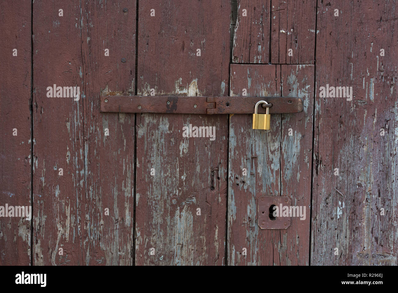 Old wooden doors locked with metal yellow lock. New yellow lock on old brown doors. Stock Photo