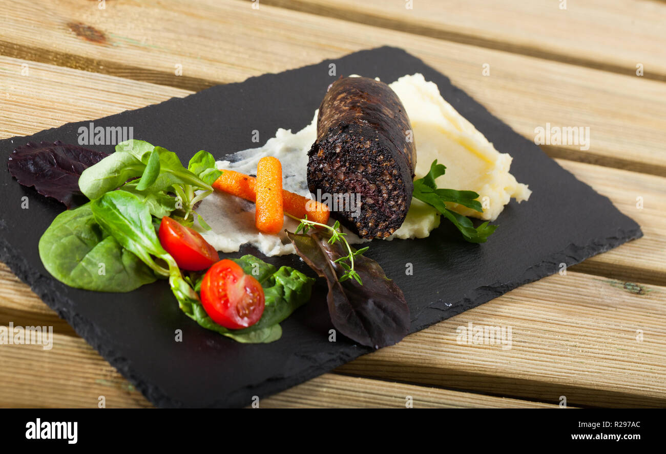 Black pudding sausage served with potato puree, vegetables and greens on slate Stock Photo