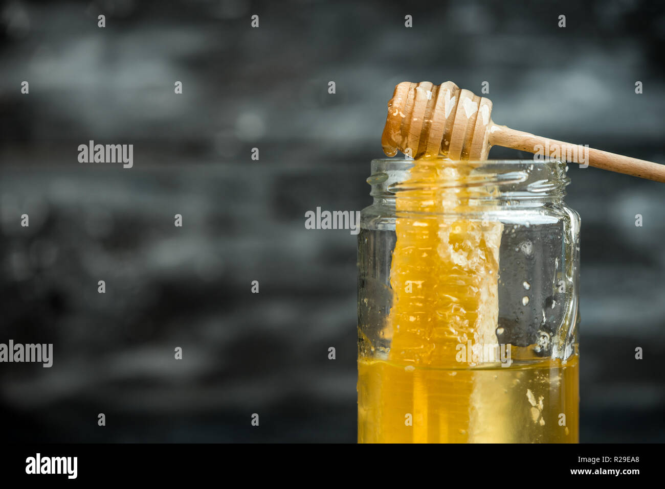 natural, healthy ingredient - a jar of golden honey on a dark background - Stock Image