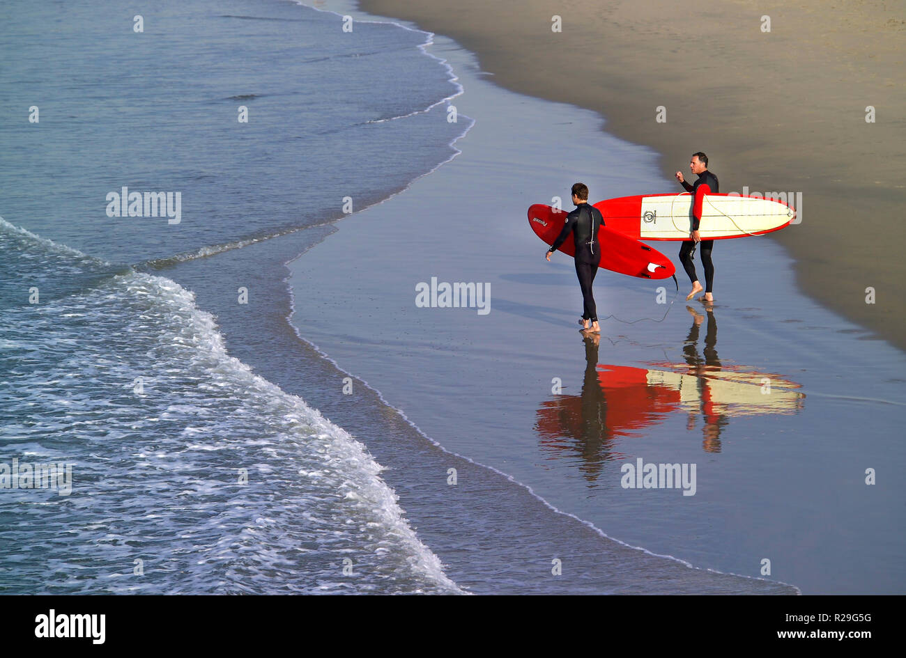Two businessmen in wetsuits head from the beach at daybreak into the Pacific Ocean with their surfboards for some pre-work recreation at Newport Beach in Southern California, USA. Dozens of beaches along the Golden State's coastline offer easy access to waves that attract surfers of all ages and abilities. - Stock Image