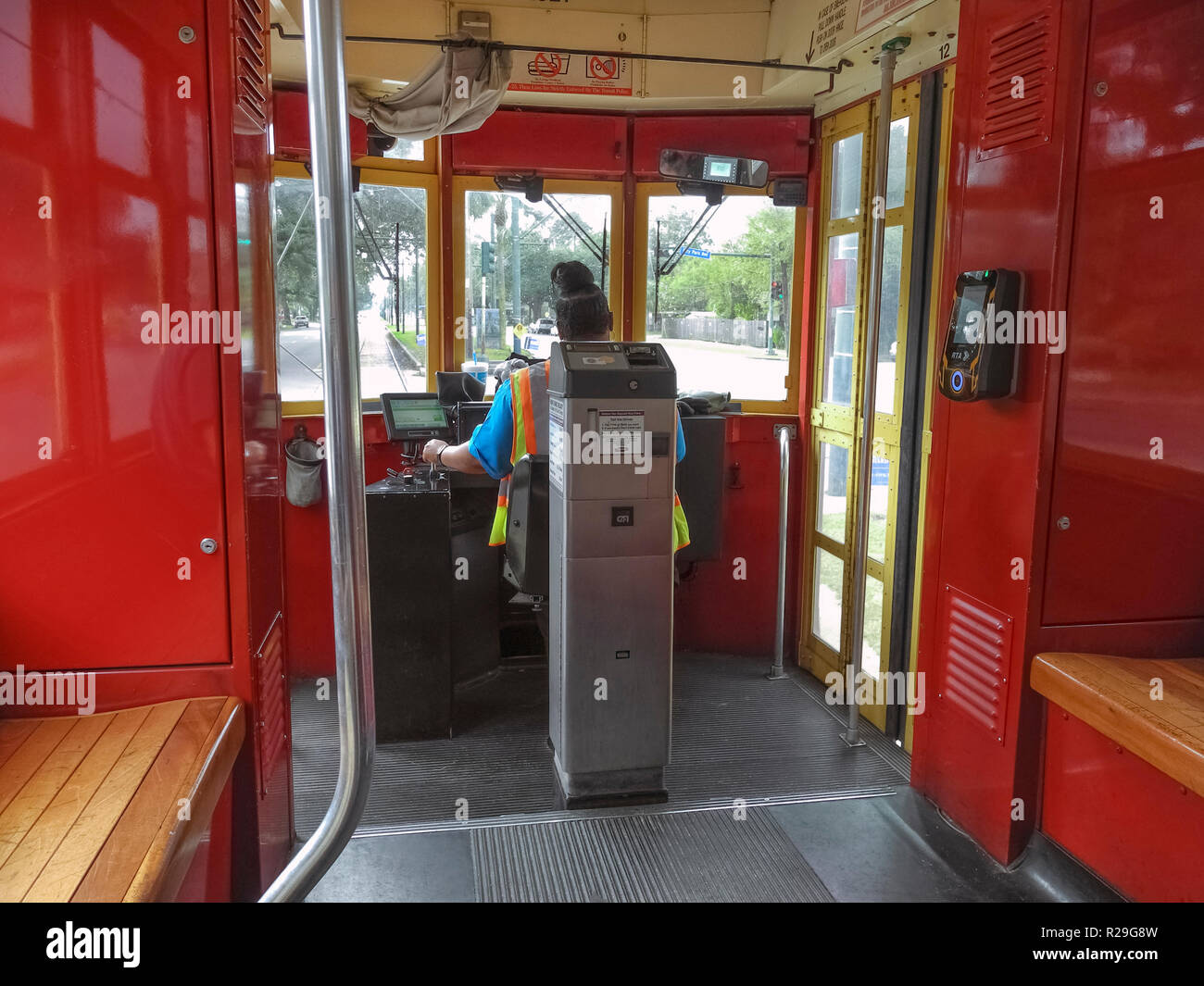 Inside a streetcar looking past the self-service ticket machine and the female driver of such historic electric vehicles that have been providing public transportation on steel rails throughout the southern city of New Orleans, Louisiana, USA, for more than a century. Twenty-five miles of track host four streetcar lines, including the iconic St. Charles line that started service in 1835 and is the oldest continuously-operating streetcar line in the world. The red car seen here travels through the heart of the city on the Canal Street line and takes about 30 minutes to ride from end to end. - Stock Image