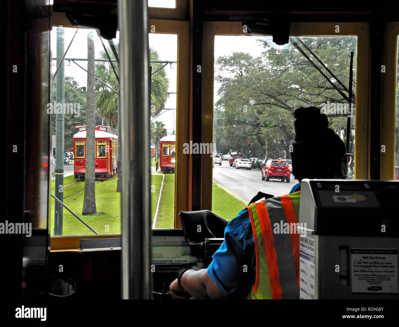 Inside a streetcar looking past the self-service ticket machine and the female driver of such historic electric vehicles that have been providing public transportation on steel rails throughout the southern city of New Orleans, Louisiana, USA, for more than a century. Twenty-five miles of track host four streetcar lines, including the iconic St. Charles line that started service in 1835 and is the oldest continuously-operating streetcar line in the world. The red cars seen here travel through the heart of the city on the Canal Street line and takes about 30 minutes to ride from end to end. - Stock Image