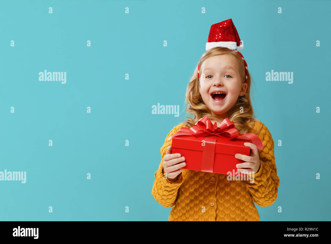 b4c82cca65f79 Happy little child girl in a warm knitted sweater and cap Santa Claus is  holding a