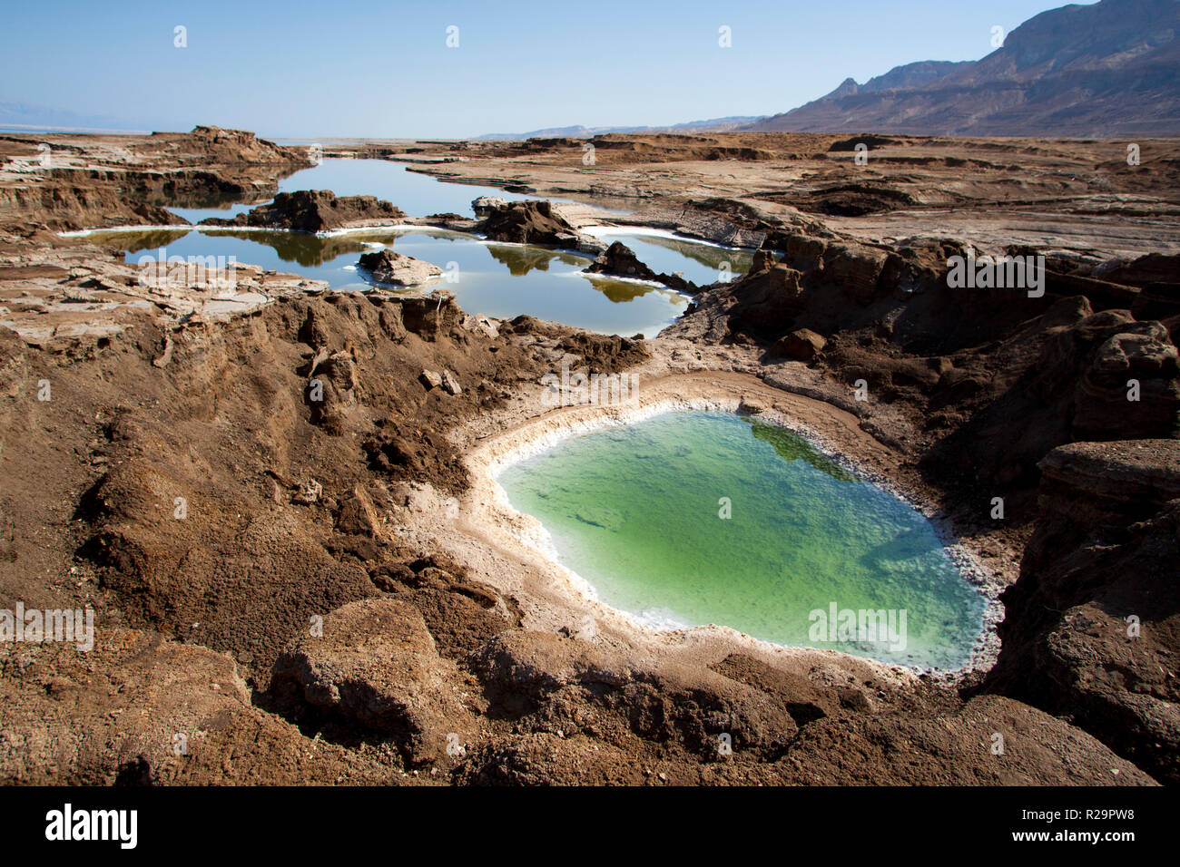 Sinkholes near the Dead Sea, formed when underground salt is dissolved by freshwater intrusion, due to continuing sea-level drop. - Stock Image
