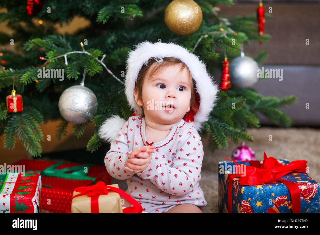 f839870669c Little smiling baby in hat of Santa Claus on a background of Christmas  garland