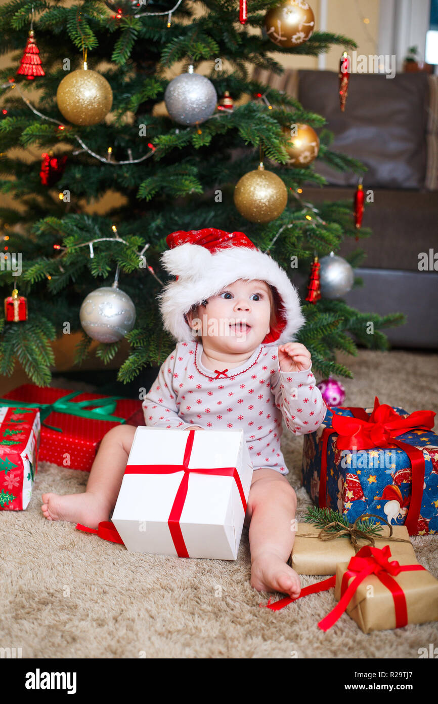 Happy cute baby girl in santa claus hat holding christmas gifts at christmas tree at home