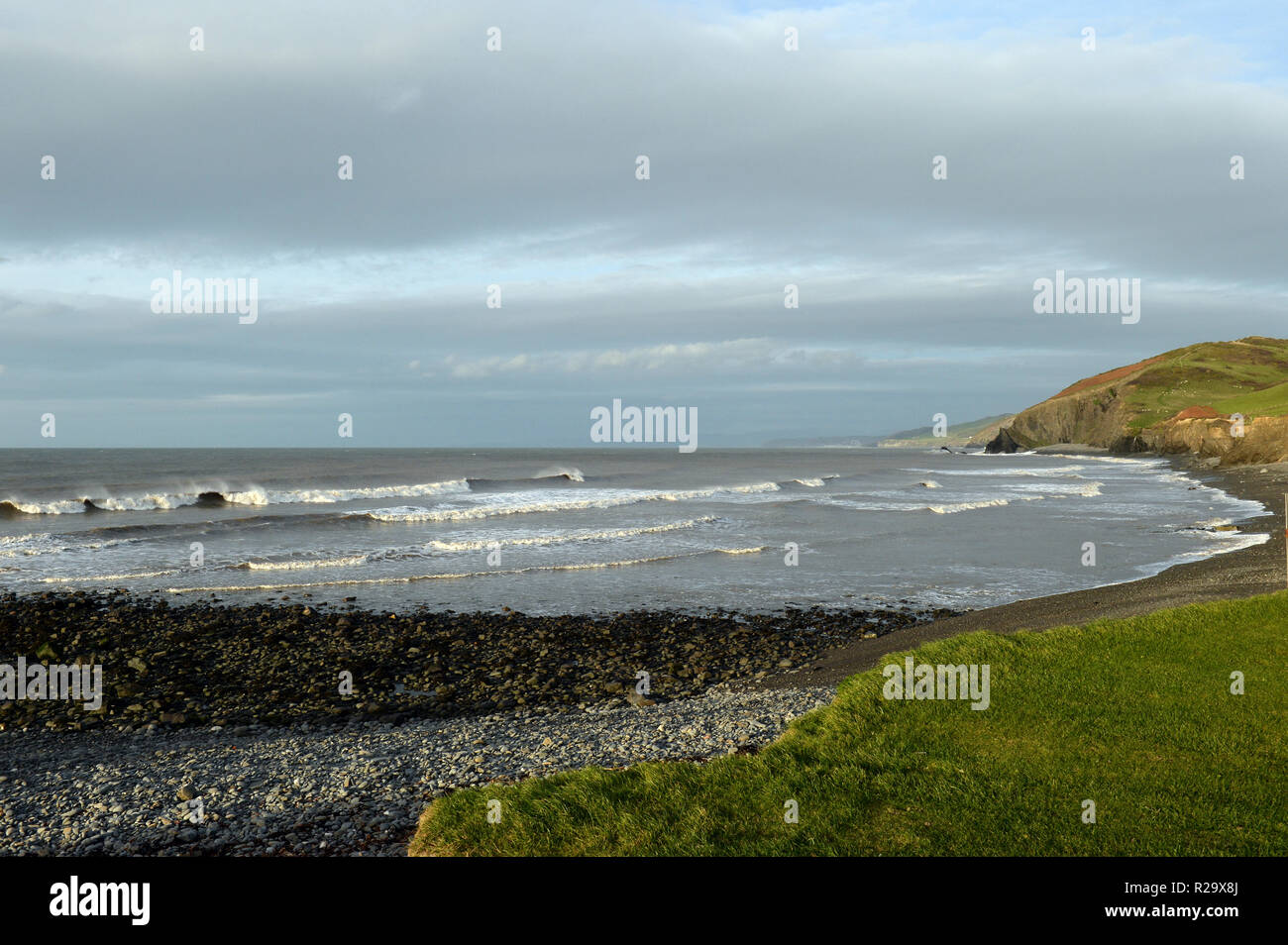 Llanrhystud beach in late evening light looking north at the coast to Aberystwyth over the surf and pebble shoreline beach - Stock Image