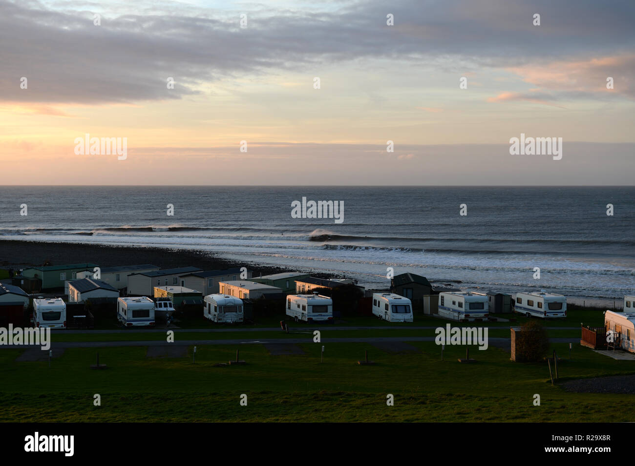 Llanrhystud beach at sunset light looking over the river mouth break and pebble shoreline with several caravans in foreground - Stock Image