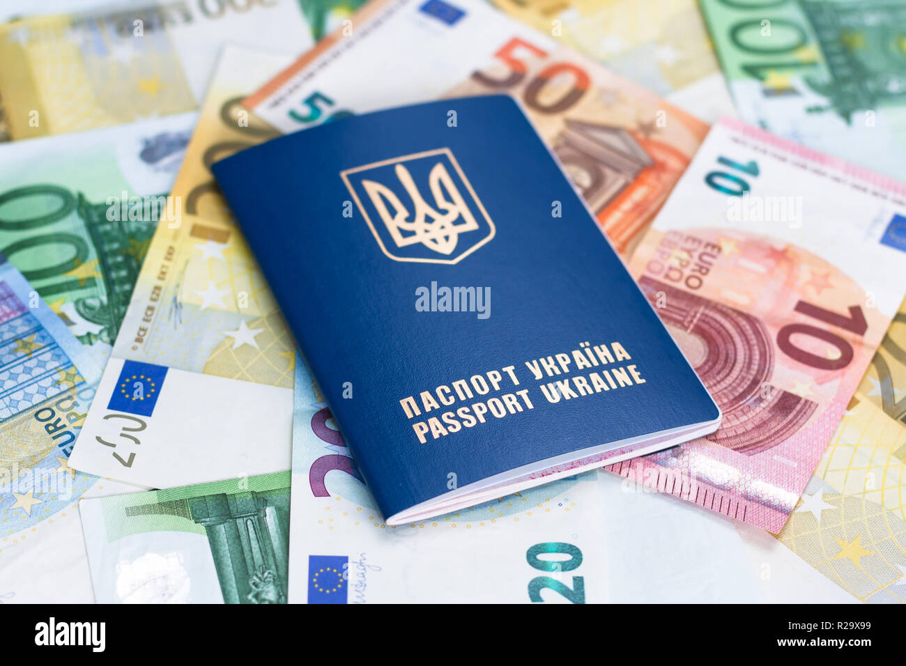 Ukranian travel passport laying on different euro banknotes. twenty, fifty,hundred,two handred, euro banknotes. - Stock Image