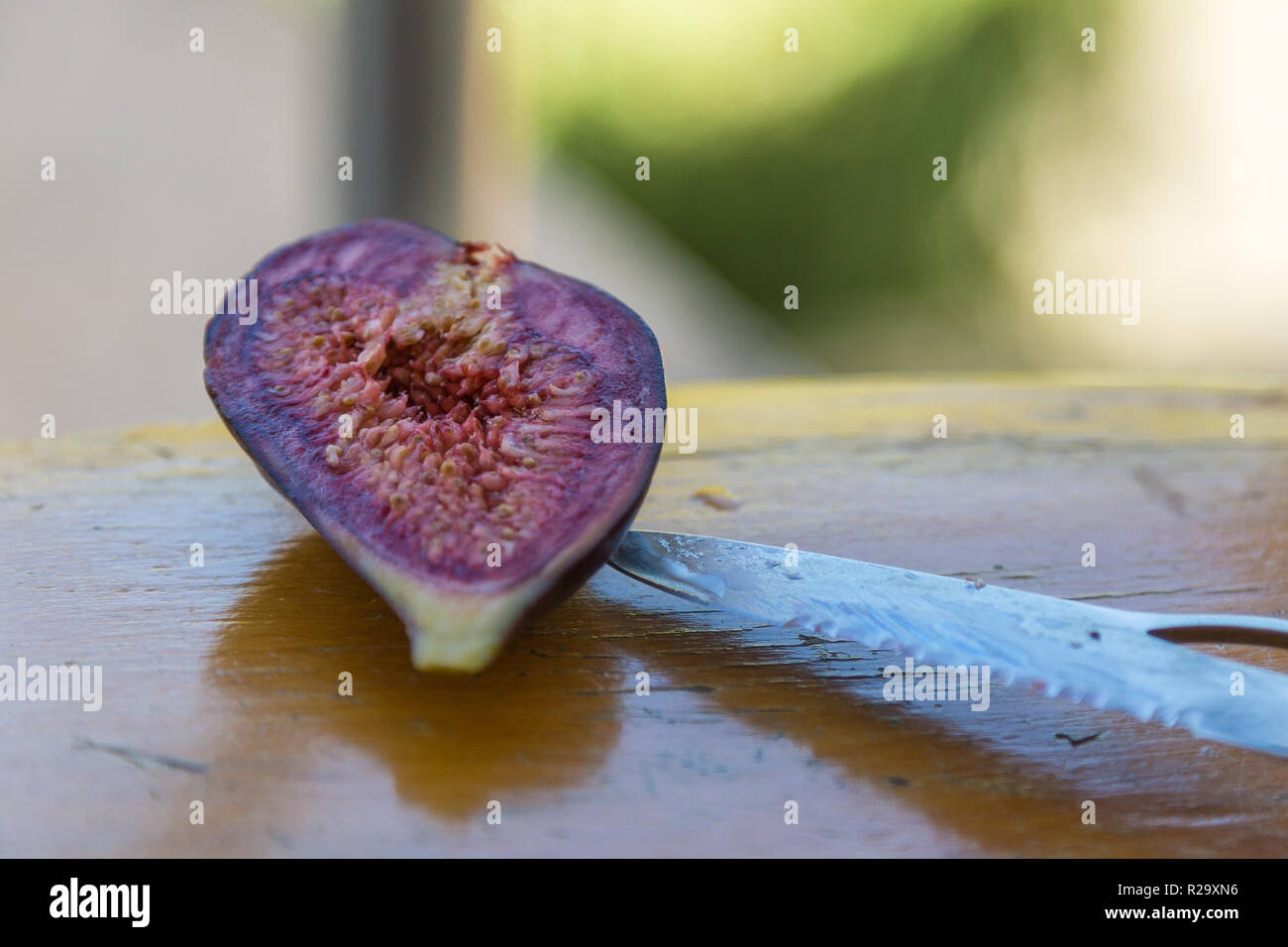 Fresh, violet, cut fig with a knife on a wooden table, Tirana, Albania. - Stock Image