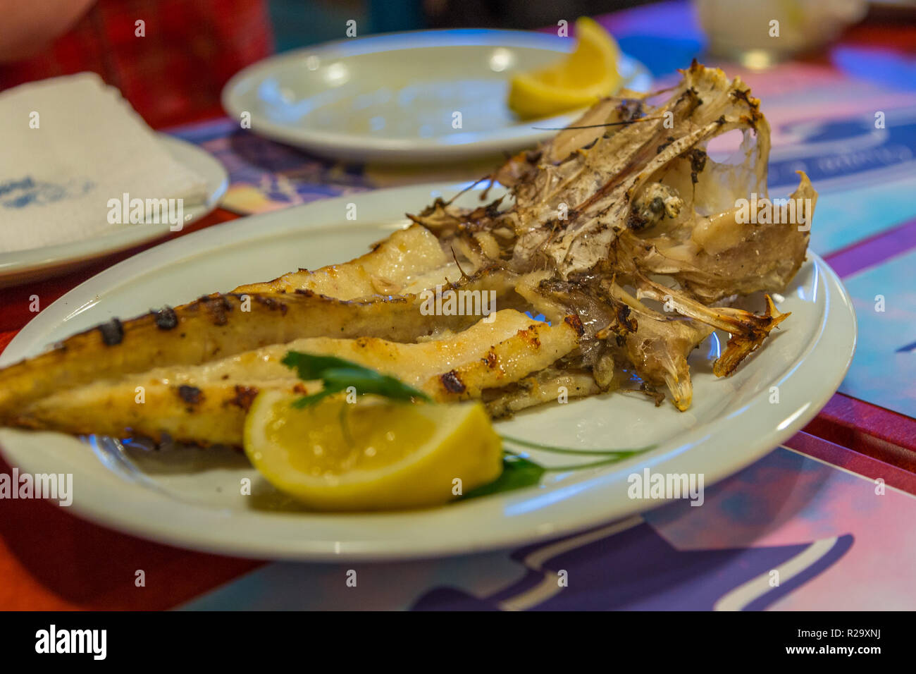 Grilled monkfish, sea fish, on a white plate with lemon. Restaurant in Tirana, Albania. - Stock Image