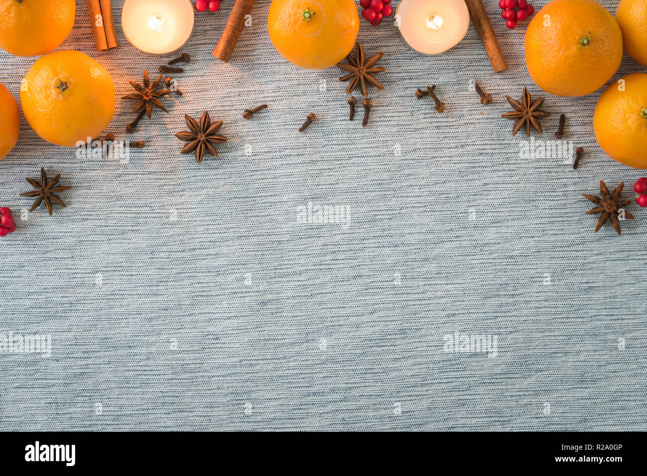 Christmas arrangement of holiday spices, oranges and candles - Stock Image