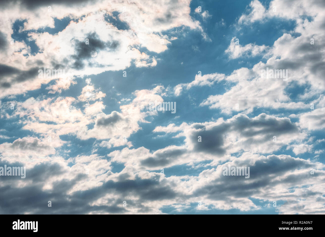 Summer bright sky with cumulus clouds and sun in the clouds - Stock Image