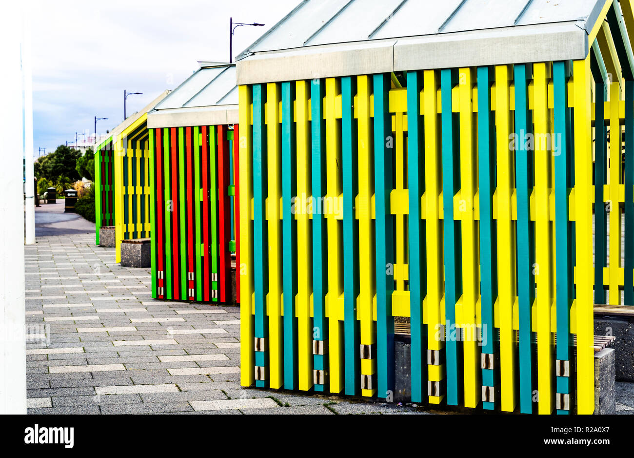Colourful sun shelters on a beach side promenade. - Stock Image