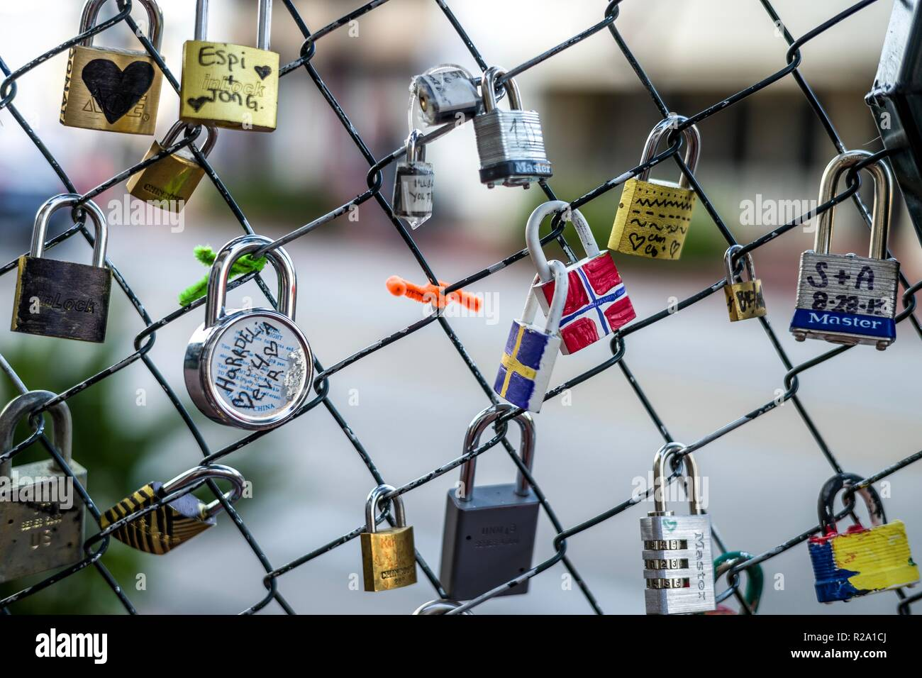Locks hanging on a fence help to collect memories of times past. - Stock Image