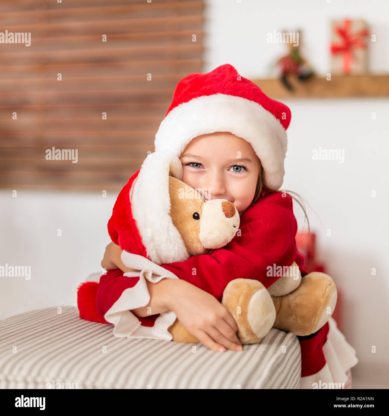 942b70b1f Cute young girl wearing santa hat hugging her christmas present, soft toy  teddy bear. Happy kid with xmas present, smiling and looking at camera.