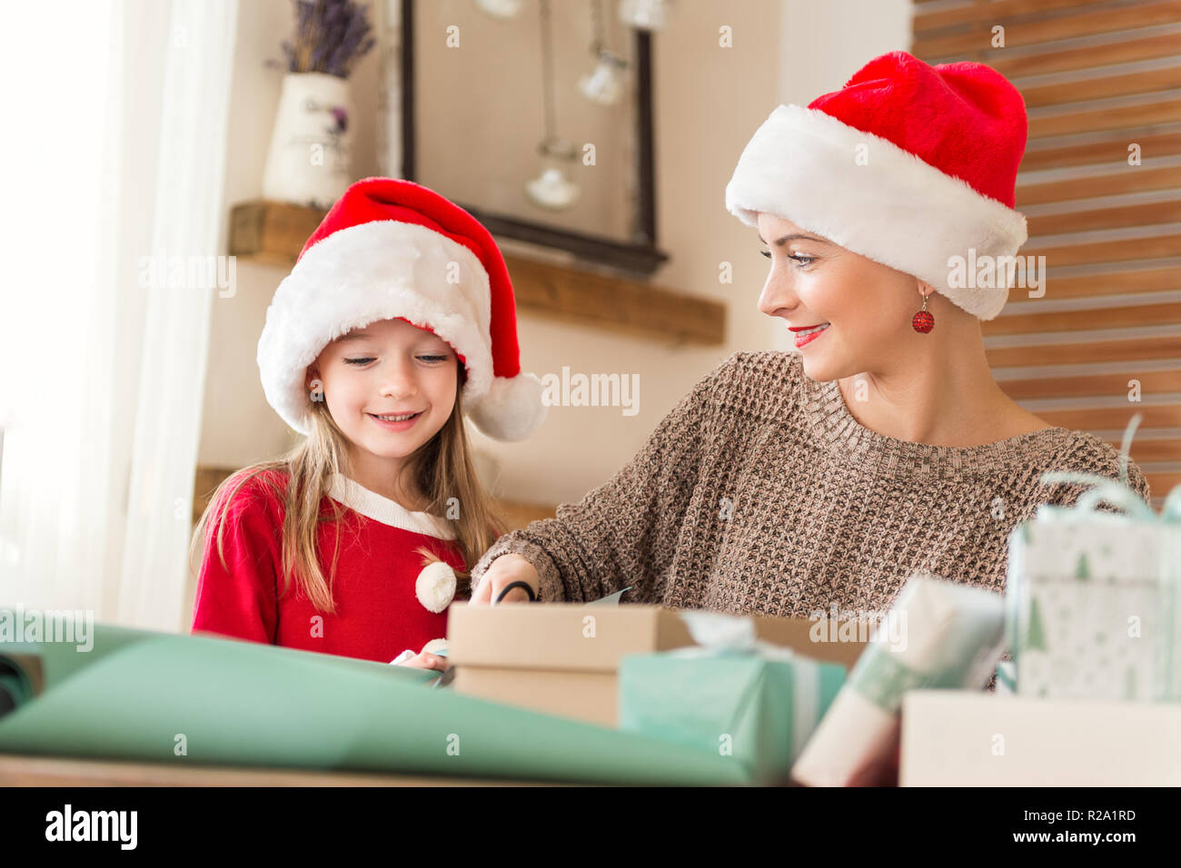 Mother Christmas.Mother And Daughter Wearing Santa Hats Having Fun Wrapping