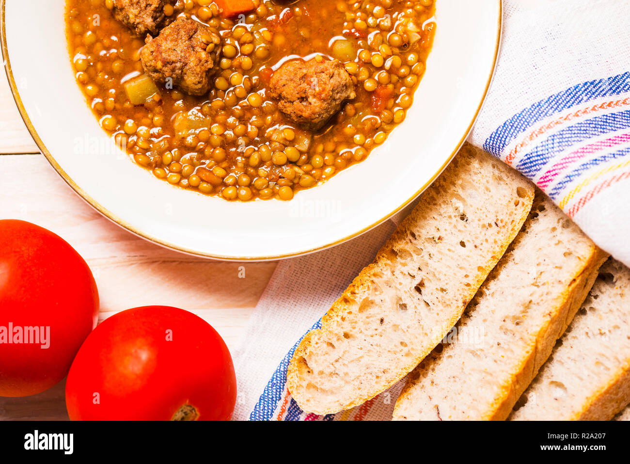 Lentil soup with fricandel, tomatoes and bread - Stock Image