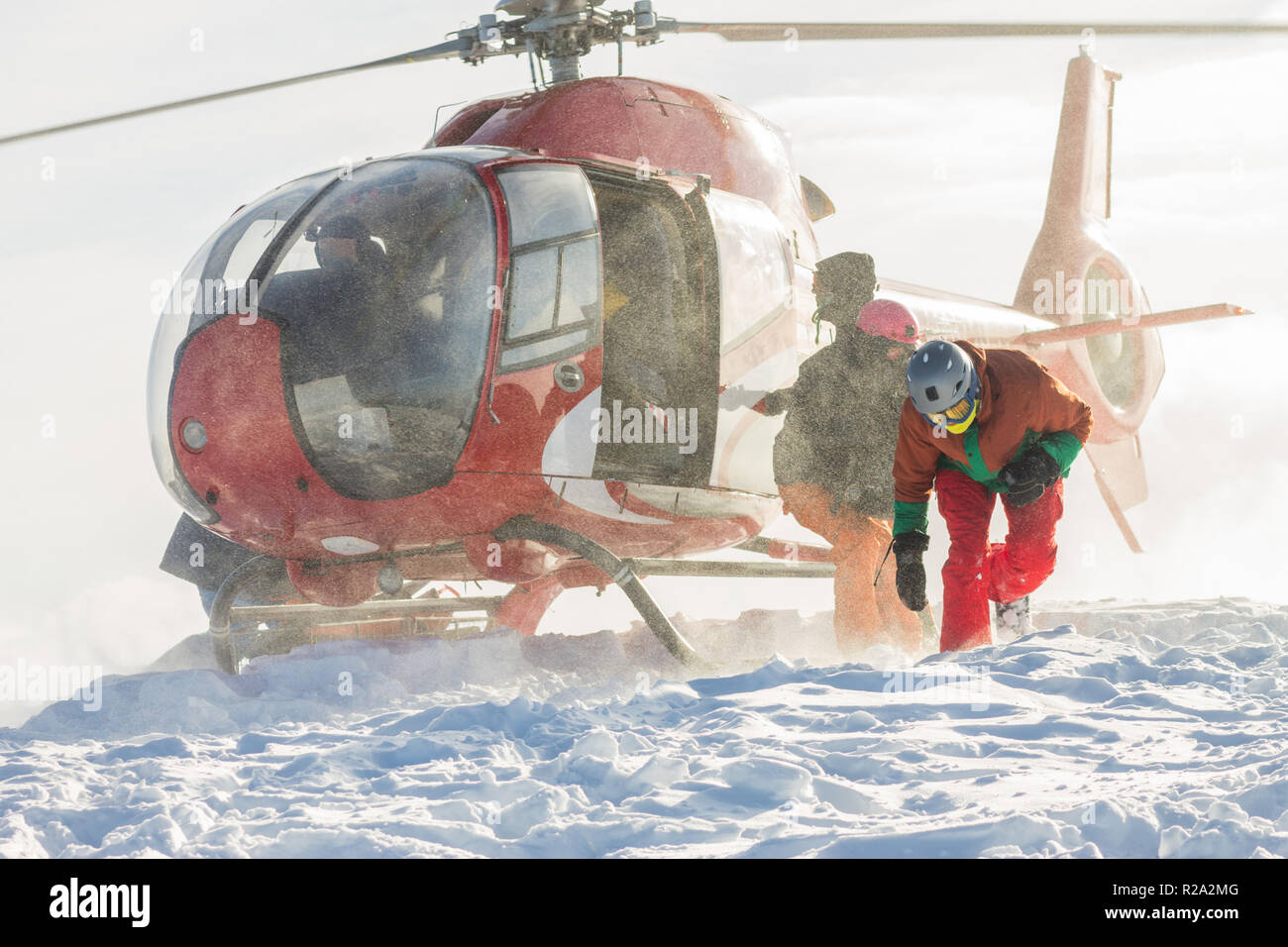 Landing people from a helicopter, freeriders snowboarders on the mountain - Stock Image