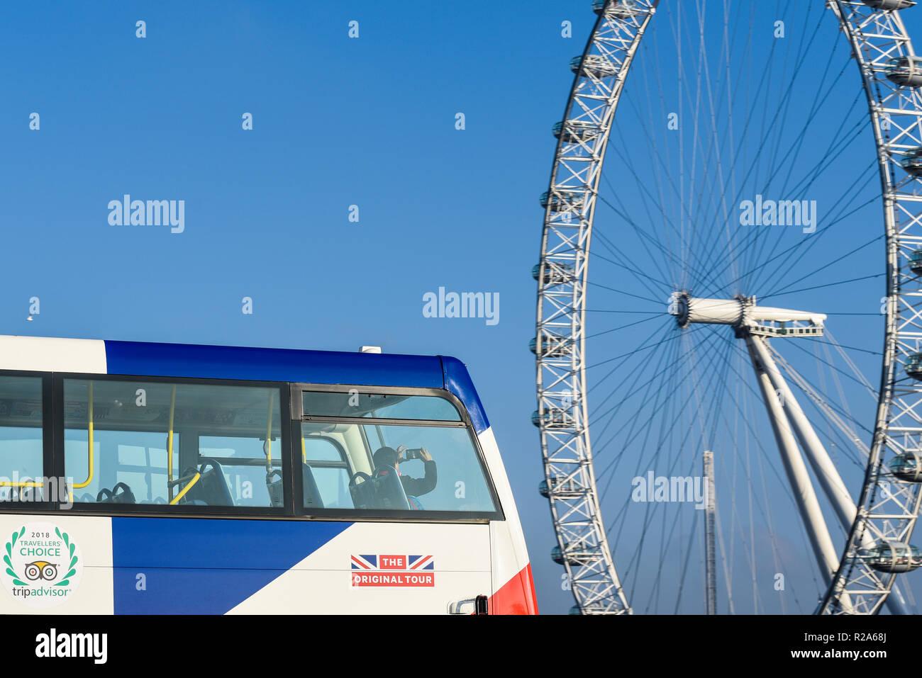 A tourist on a British tour bus taking a mobile phone camera phone photograph of the London Eye, Millennium Wheel. Tripadvisor, the Original Tour - Stock Image