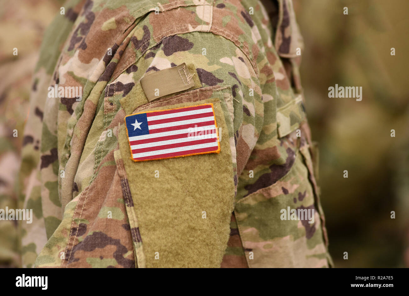 Liberia flag on soldiers arm. Liberia troops (collage) - Stock Image