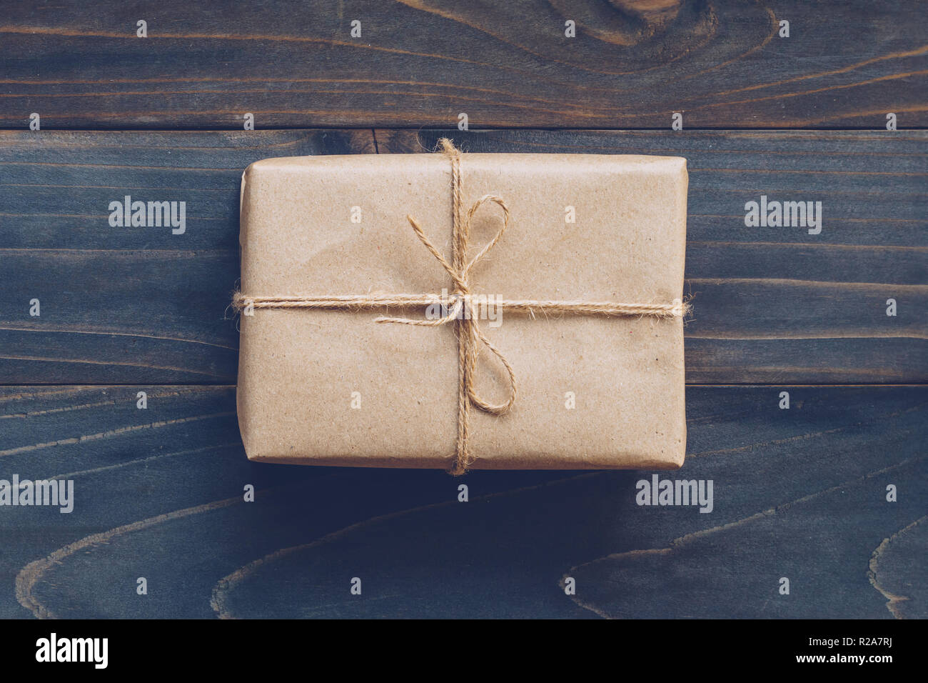 String or twine tied in a bow on kraft paper gift box no wooden table texture and background. - Stock Image