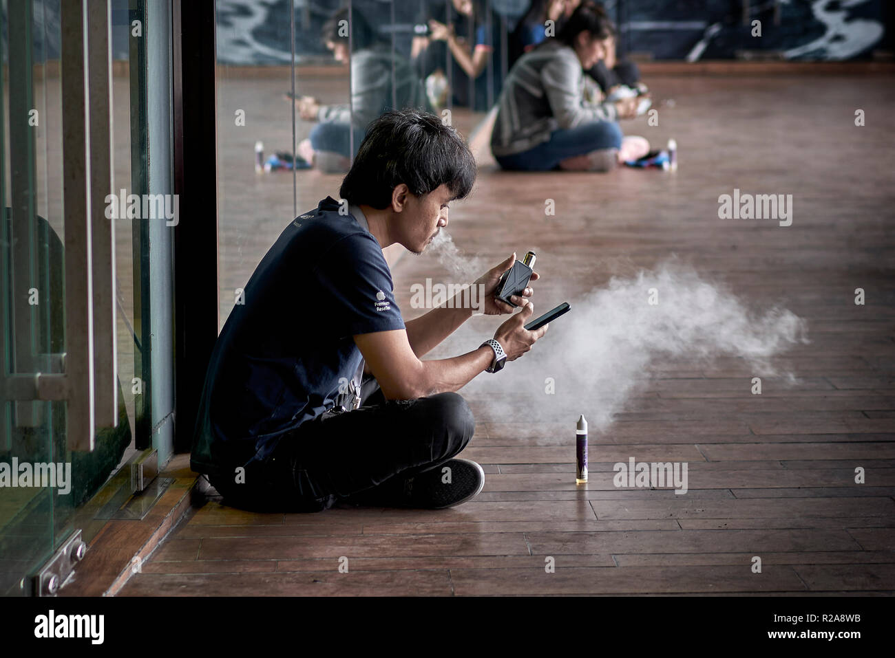 Vaping. Man smoking an e cigarette and blowing a large cloud of smoke - Stock Image