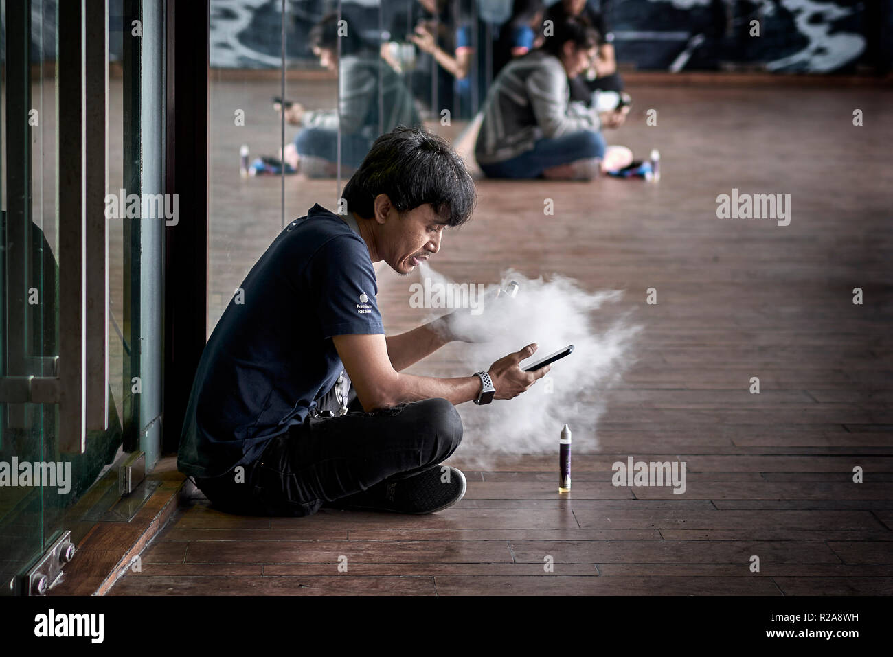 Vaping. Man smoking an e cigarette and blowing a large cloud of smoke Stock Photo