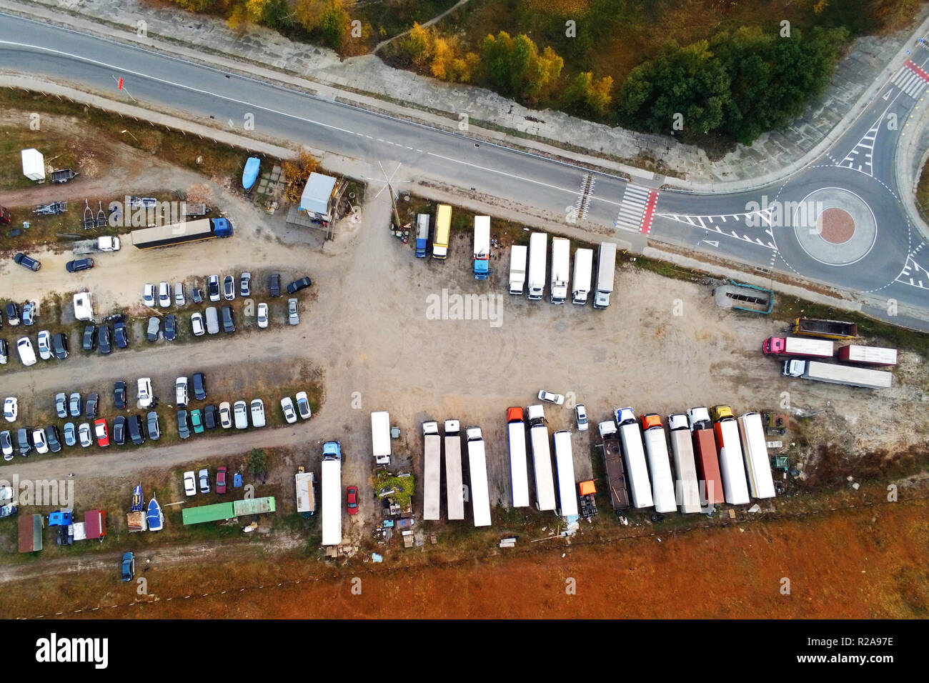 Aerial view of unpaved natural parking with lots of trucks, trailers and cars. Rest place near road and circle junction - Stock Image