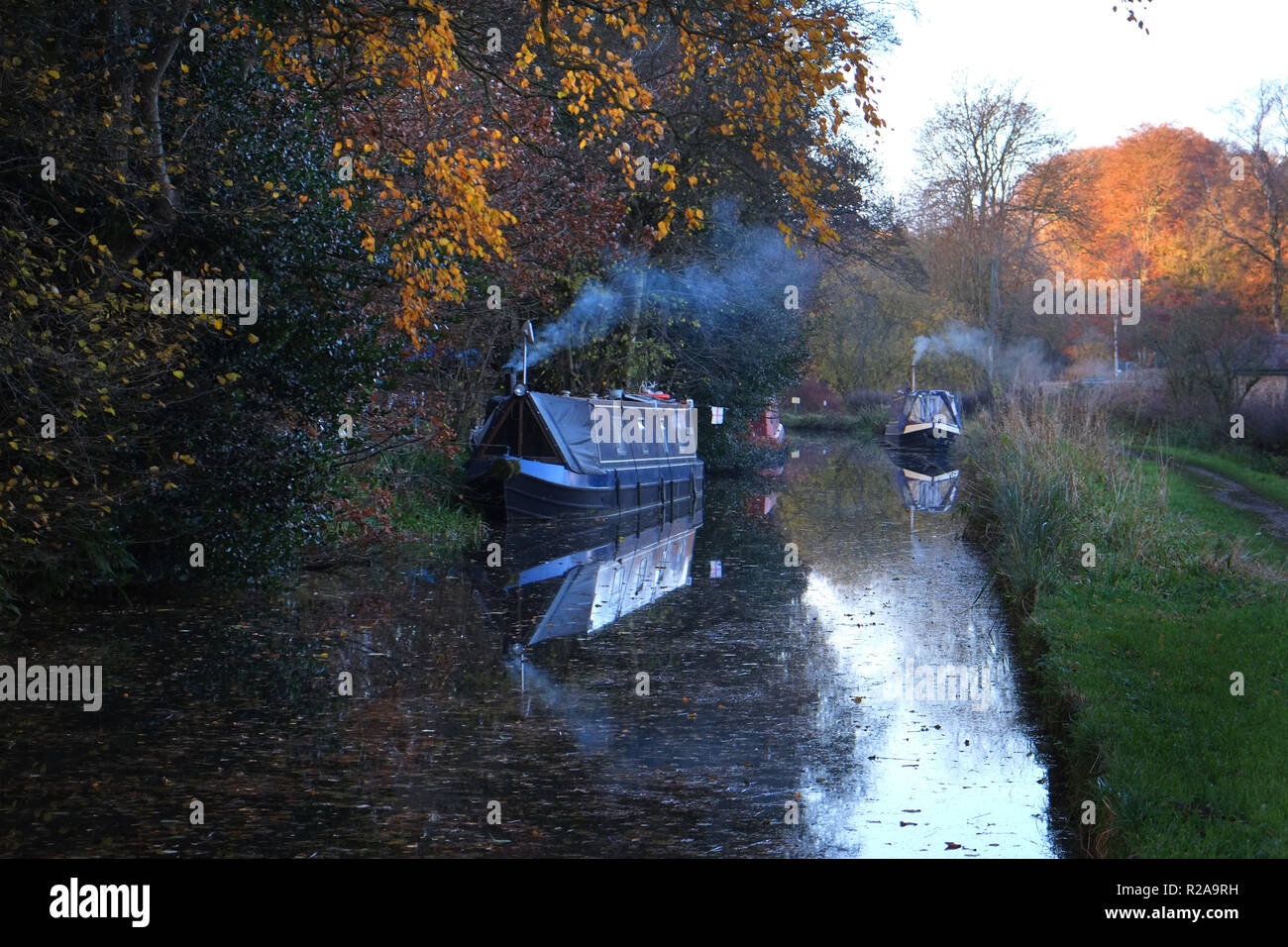 Narrow boats with smoking chimneys moored along the banks of the Caldon Canal at Cheddleton, Staffordshire Moorlands, England. Golden autumn light shines on the trees - Stock Image
