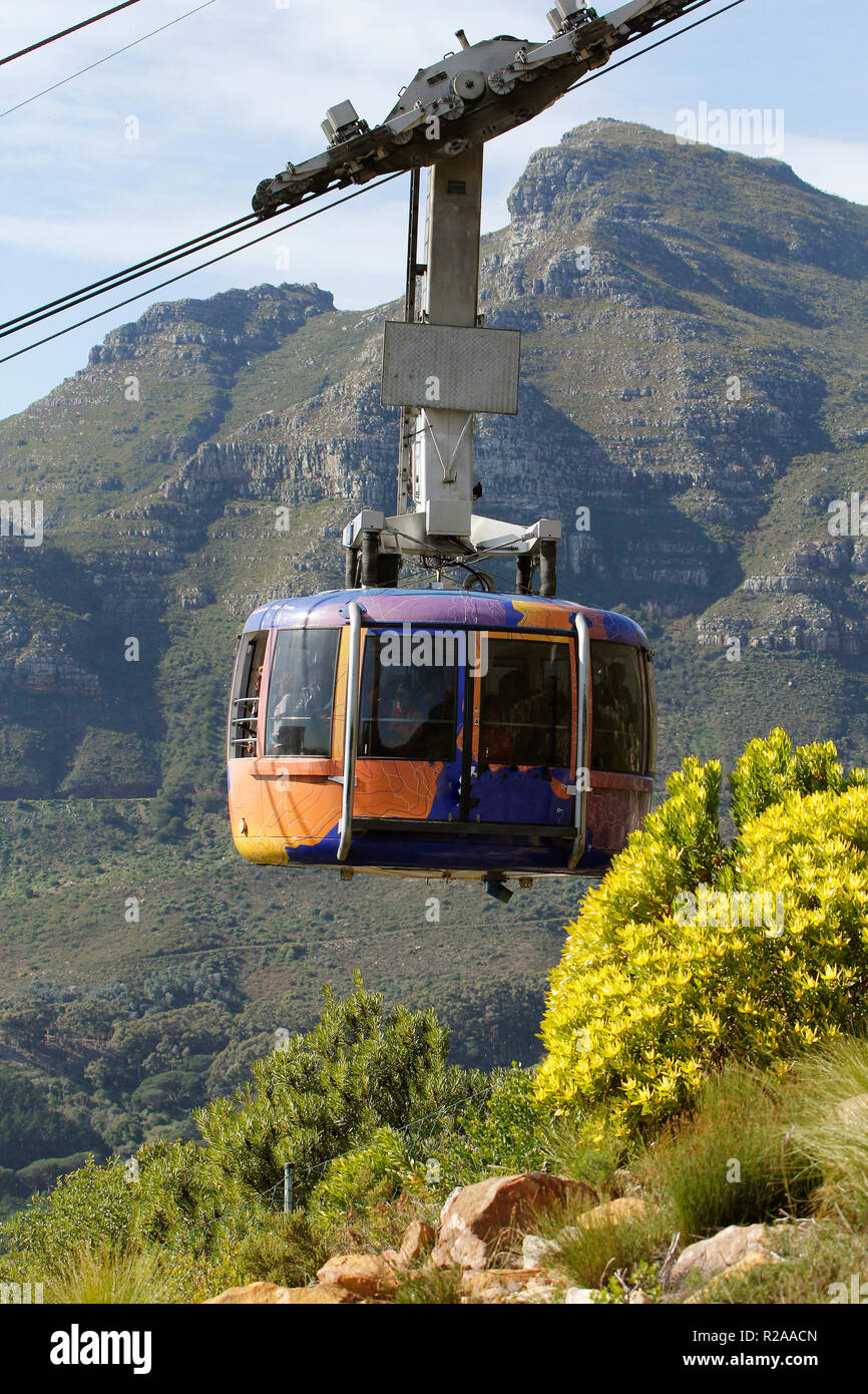 One of the Table Mountain cablecars on its way up to the top of Table Mountain, with Devils Peak behind. - Stock Image